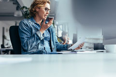 Коммерсантка говоря на умном телефоне с клиентом Стоковая Фотография