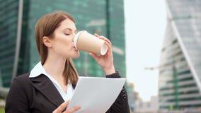 Коммерсантка городская, профессиональный женский работодатель идя к встречать документы выпивая кофе акции видеоматериалы