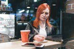 Коммерсантка, девушка держа ручку, писать в тетради, ноутбук в кафе, смартфоне, ручке, компьютере пользы r стоковое изображение