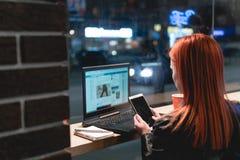 Коммерсантка, девушка работая на ноутбуке в кафе, смартфоне в руках, ручке владением, телефоне пользы r Онлайн, стоковые изображения