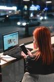 Коммерсантка, девушка работая на ноутбуке в кафе, смартфоне в руках, ручке владением, телефоне пользы r Онлайн, стоковые изображения rf