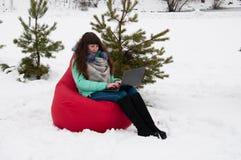 Коммерсантка девушки сидя с компьтер-книжкой в стуле в парке зимы Работа и отдых в то же время Стоковые Изображения RF