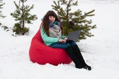 Коммерсантка девушки сидя с компьтер-книжкой в стуле в парке зимы Работа и отдых в то же время Стоковые Изображения