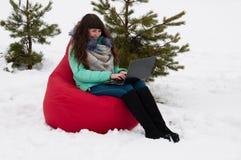 Коммерсантка девушки сидя с компьтер-книжкой в стуле в парке зимы Работа и отдых в то же время Стоковая Фотография RF