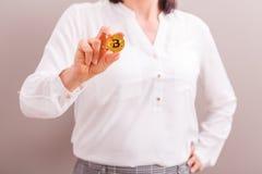 Коммерсантка держа золотую монетку bitcoin стоковое фото