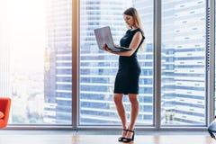 Коммерсантка держа компьтер-книжку стоя в современном офисе против окна с видом на город Стоковое фото RF