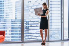 Коммерсантка держа компьтер-книжку стоя в современном офисе против окна с видом на город Стоковые Фото