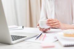Коммерсантка держа чашку кофе пока работающ с компьтер-книжкой на рабочем месте Стоковое Фото