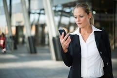 коммерсантка ее мобильный телефон используя стоковые изображения