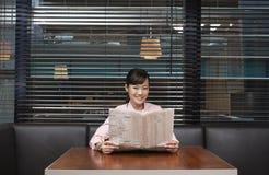 Коммерсантка держа газету на таблице кафа Стоковые Фото