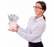 Коммерсантка держа копилку и долларовые банкноты Стоковая Фотография