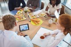 Коммерсантка держа кофейную чашку пока коллеги используя цифровые таблетки вокруг таблицы завтрака Стоковое Изображение