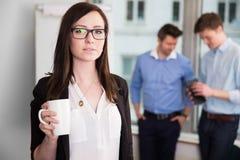 Коммерсантка держа кружку кофе пока коллеги обсуждая внутри Стоковое Фото