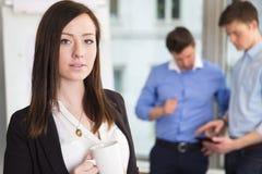 Коммерсантка держа кружку кофе при коллеги обсуждая в b Стоковое Изображение RF