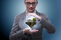 Коммерсантка держа остров летания в концепции eco Стоковые Изображения