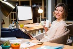 Коммерсантка держа цифровые таблетку и кофейную чашку на ее столе Стоковое Изображение