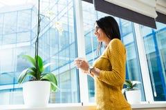 Коммерсантка держа чашку с кофе и смотря окно Стоковое Изображение RF
