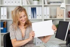 Коммерсантка держа чистый лист бумаги на столе офиса Стоковое фото RF