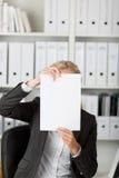 Коммерсантка держа чистый лист бумаги перед стороной Стоковое Изображение RF