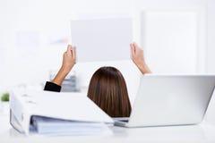 Коммерсантка держа чистый лист бумаги с связывателем и компьтер-книжку на столе Стоковая Фотография