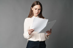 Коммерсантка держит бумаги в ее руках и читает что написано там на серой предпосылке Стоковое фото RF