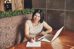 Коммерсантка детенышей усмехаясь кавказская с компьтер-книжкой и тетрадью Женщина в кафе Стоковые Изображения
