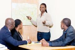 Коммерсантка делает представление на офисе на встрече на стоковое изображение