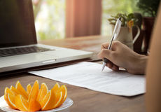 Коммерсантка заполняя на форме документа с свежим апельсином и не Стоковое Фото
