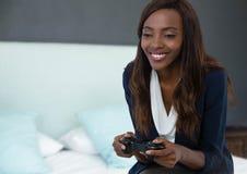Коммерсантка играя с регулятором компютерной игры с предпосылкой спальни Стоковые Фотографии RF