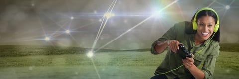 Коммерсантка играя с регулятором компютерной игры с светлыми соединениями на предпосылке зеленых холмов Стоковые Фото