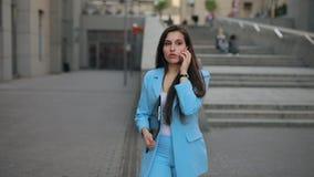 Коммерсантка идет домой после работы говоря по телефону акции видеоматериалы