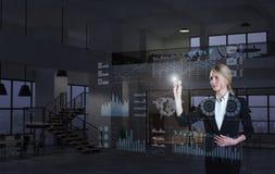Коммерсантка используя диаграммы на виртуальном дисплее стоковое изображение