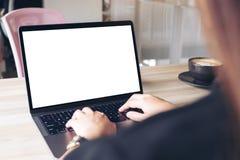Коммерсантка используя и печатающ на компьтер-книжке с пустым белым экраном настольного компьютера с кофейной чашкой на деревянно Стоковое фото RF