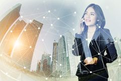 Коммерсантка используя мобильный телефон и смотрящ вперед к городу w Стоковые Изображения