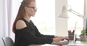 Коммерсантка используя ноутбук и делающ обработку документов на офисе акции видеоматериалы