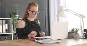 Коммерсантка используя ноутбук и сочинительство в, который хранят документах видеоматериал