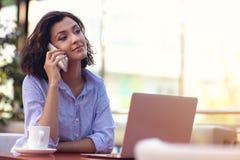Коммерсантка используя телефон пока работающ в кофейне стоковое фото