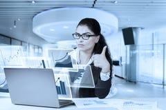 Коммерсантка используя компьтер-книжку и показывающ большой палец руки вверх Стоковые Изображения RF