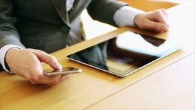 Коммерсантка используя планшет и умный телефон на столе сток-видео