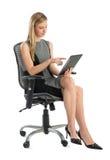 Коммерсантка используя таблетку цифров пока сидящ на стуле офиса Стоковые Изображения