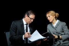 Коммерсантка используя цифровую таблетку и смотрящ контракт бизнесмена подписывая Стоковое Изображение RF