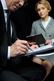 Коммерсантка используя цифровую таблетку пока контракт бизнесмена подписывая Стоковые Изображения