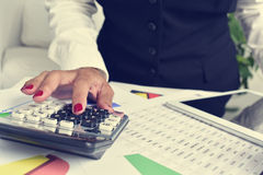 Коммерсантка используя электронный калькулятор в ее офисе Стоковое фото RF