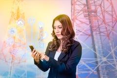 Коммерсантка используя smartphone и значок стоковое фото