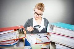 Коммерсантка исследует документы с большим loupe Стоковая Фотография