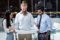 Коммерсантка и бизнесмены обсуждая над светокопией Стоковое Фото