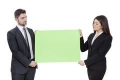 Коммерсантка и бизнесмен держа шильдик Стоковое Изображение