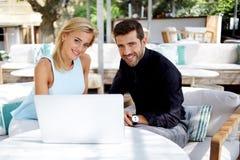 Коммерсантка и бизнесмен используя портативный компьютер во время пролома работы в кафе Стоковая Фотография
