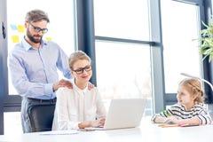 Коммерсантка и бизнесмен при eyeglasses работая при дочь компьтер-книжки рисуя близко в офисе Стоковые Фотографии RF