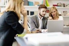 Коммерсантка и бизнесмен работая в офисе стоковые изображения